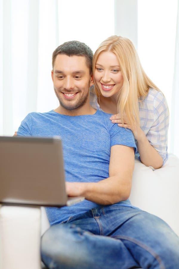 Χαμογελώντας ευτυχές ζεύγος με το lap-top στο σπίτι στοκ εικόνες με δικαίωμα ελεύθερης χρήσης