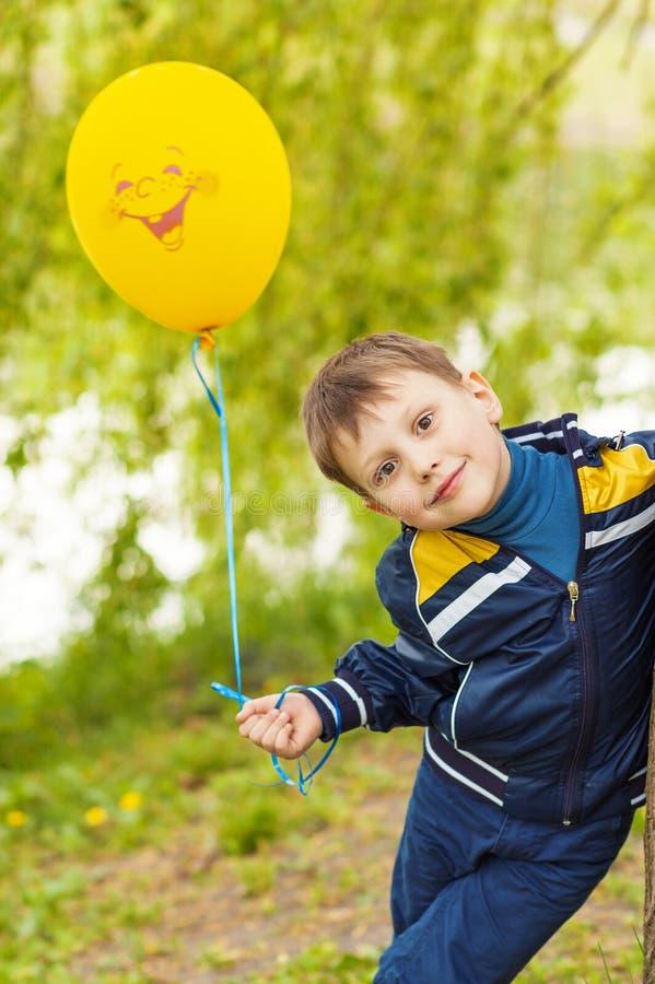Χαμογελώντας ευτυχές κίτρινο μπαλόνι αγοριών whith στοκ εικόνα