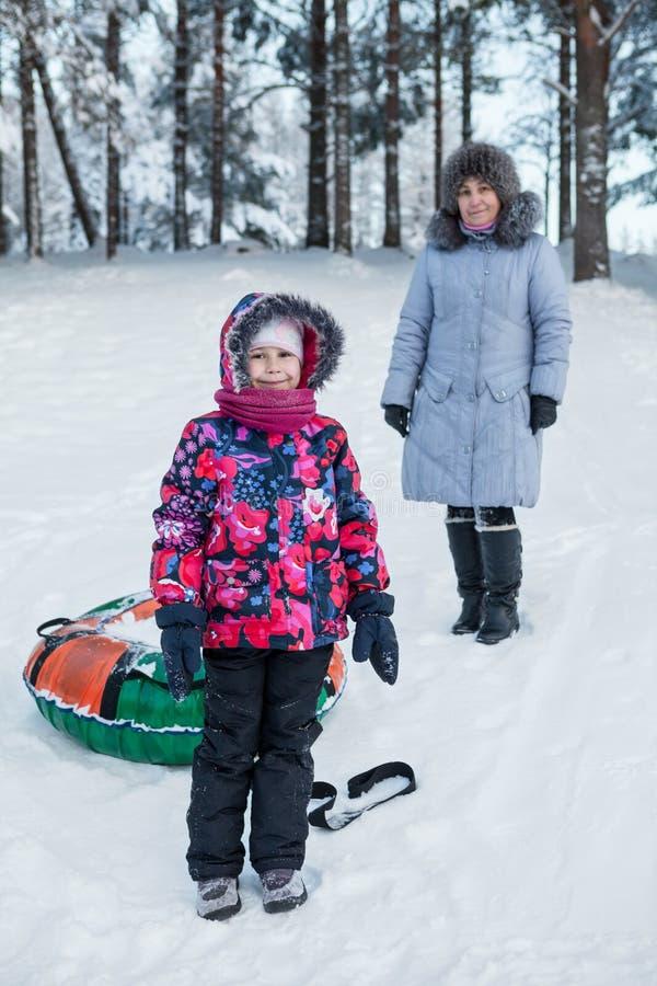 Χαμογελώντας ευτυχές παιδί με την ώριμη μητέρα ενώ σωλήνωση στο χειμερινό δάσος στοκ εικόνες με δικαίωμα ελεύθερης χρήσης