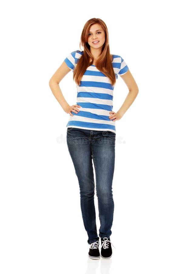 Χαμογελώντας εφηβική γυναίκα με τα χέρια στα ισχία στοκ εικόνες