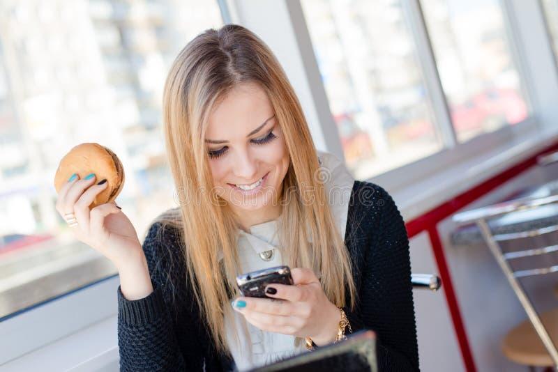 Χαμογελώντας ελκυστική νέα επιχειρησιακή γυναίκα που τρώει εύγευστο burger σε έναν καφέ ή ένα εστιατόριο που κρατά κινητό τηλεφων στοκ φωτογραφία