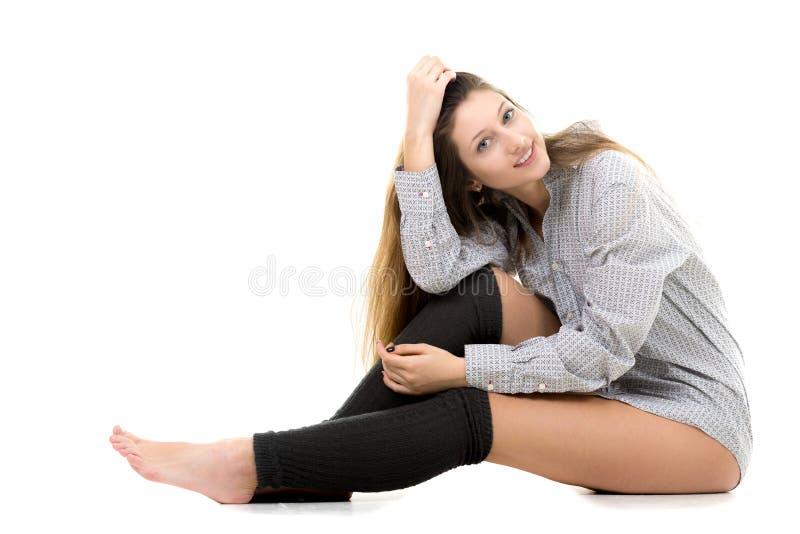Χαμογελώντας ελκυστικό νέο κορίτσι στο πουκάμισο και τις περικνημίδες στοκ εικόνες