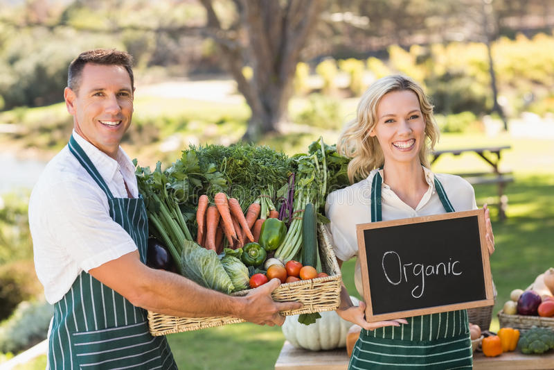 Χαμογελώντας ζεύγος αγροτών που κρατά ένα φυτικό καλάθι στοκ εικόνα