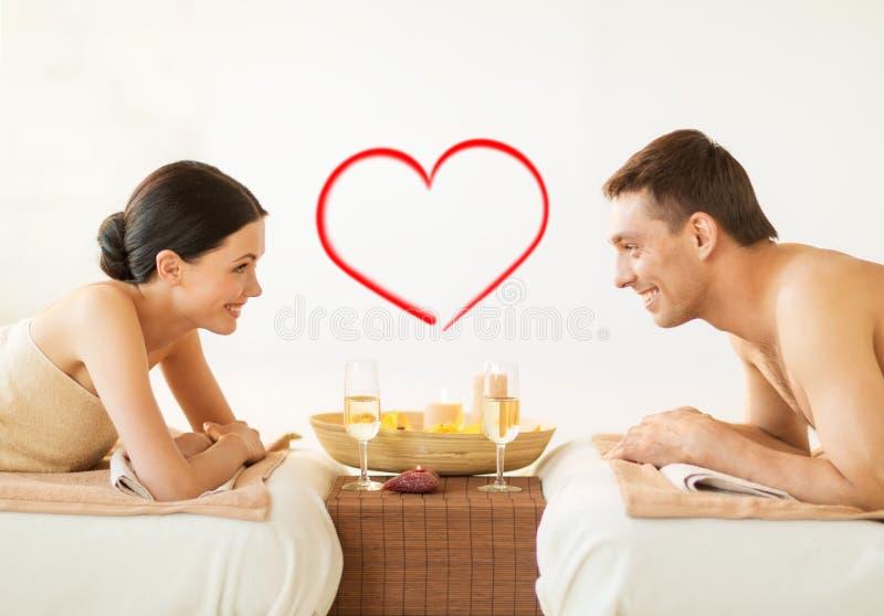 Χαμογελώντας ζεύγος με τα κεριά και τα ποτά στη SPA στοκ φωτογραφία με δικαίωμα ελεύθερης χρήσης