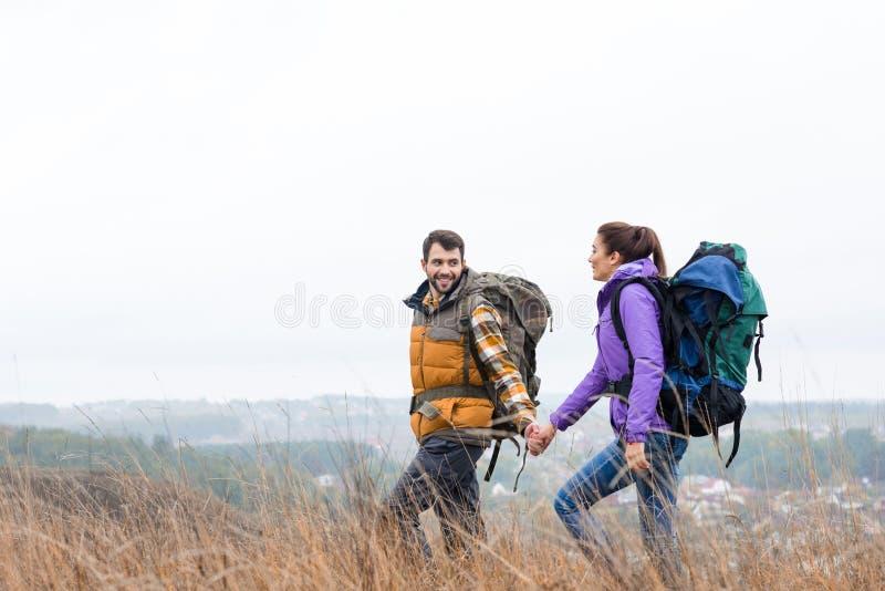 Χαμογελώντας ζεύγος με τα σακίδια πλάτης που περπατά στη χλόη στοκ εικόνες