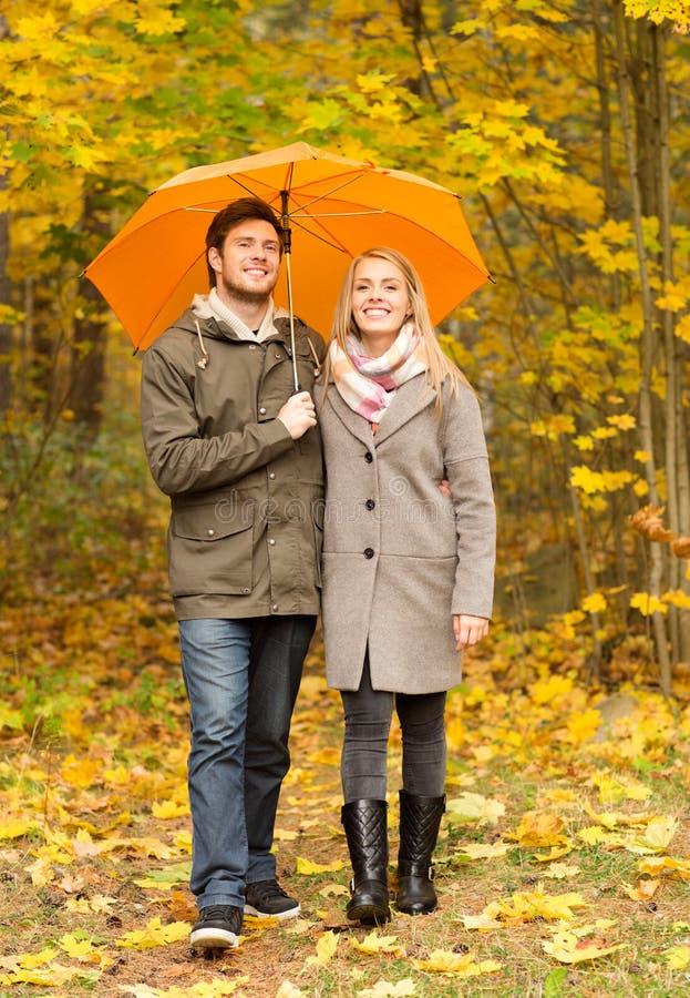 Χαμογελώντας ζεύγος με την ομπρέλα στο πάρκο φθινοπώρου στοκ φωτογραφία με δικαίωμα ελεύθερης χρήσης