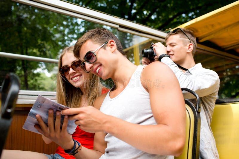 Χαμογελώντας ζεύγος με το βιβλίο που ταξιδεύει με το τουριστηκό λεωφορείο στοκ φωτογραφία με δικαίωμα ελεύθερης χρήσης