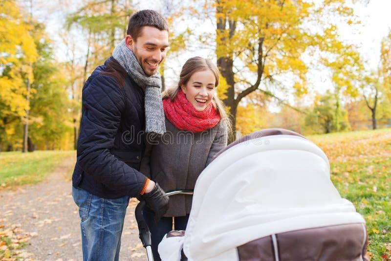 Χαμογελώντας ζεύγος με το καροτσάκι μωρών στο πάρκο φθινοπώρου στοκ φωτογραφίες