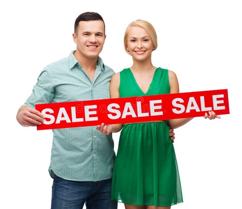 Χαμογελώντας ζεύγος με το σημάδι πώλησης στοκ φωτογραφίες με δικαίωμα ελεύθερης χρήσης