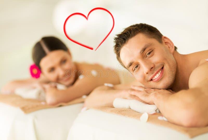 Χαμογελώντας ζεύγος που βρίσκεται στον πίνακα μασάζ στο σαλόνι SPA στοκ εικόνες