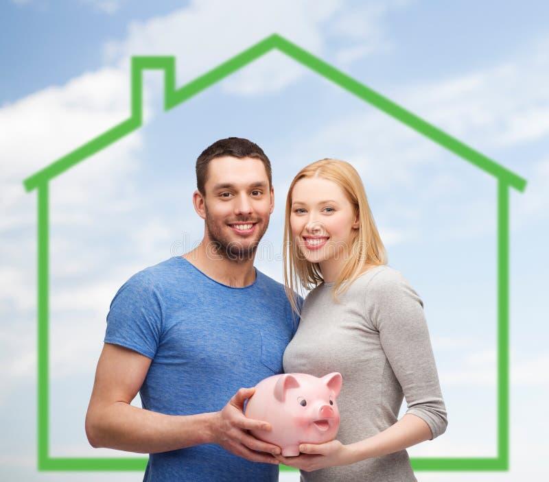 Χαμογελώντας ζεύγος που κρατά τη piggy τράπεζα πέρα από το θερμοκήπιο στοκ εικόνες