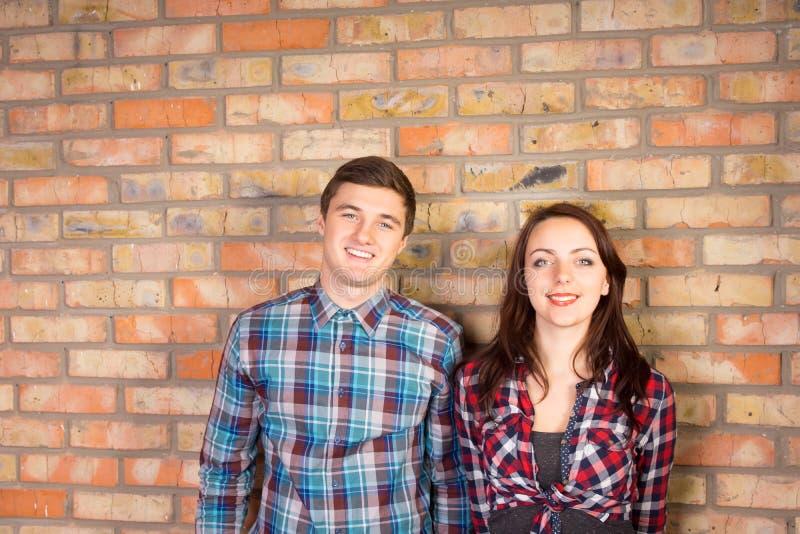 Χαμογελώντας ζεύγος που στέκεται μπροστά από το τουβλότοιχο στοκ εικόνα