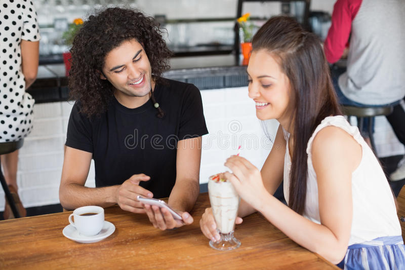 Χαμογελώντας ζεύγος που χρησιμοποιεί το κινητό τηλέφωνο ενώ έχοντας τα ποτά στο εστιατόριο στοκ εικόνες με δικαίωμα ελεύθερης χρήσης