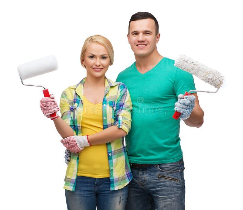 Χαμογελώντας ζεύγος στα γάντια με τους κυλίνδρους χρωμάτων στοκ φωτογραφίες με δικαίωμα ελεύθερης χρήσης