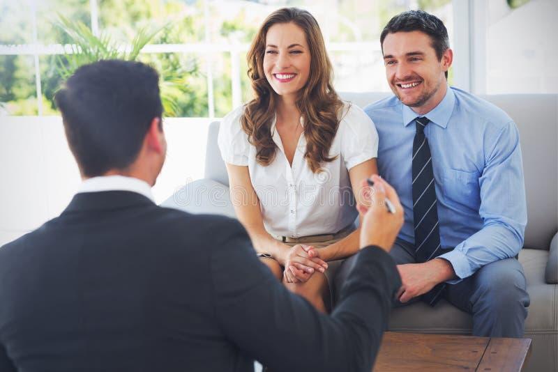 Χαμογελώντας ζεύγος στη συνεδρίαση με έναν οικονομικό σύμβουλο απεικόνιση αποθεμάτων