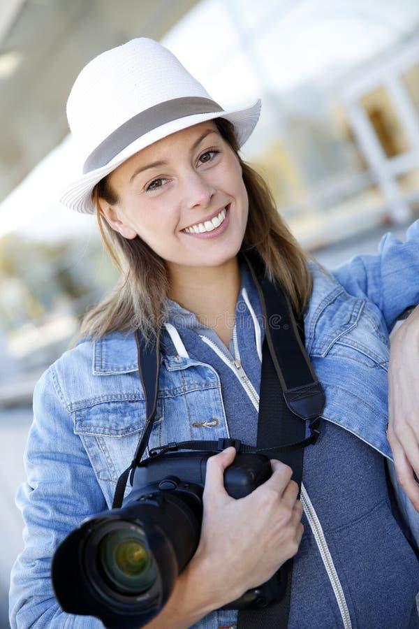Χαμογελώντας δημοσιογράφος που κρατά μια ανακλαστική κάμερα στοκ φωτογραφία με δικαίωμα ελεύθερης χρήσης