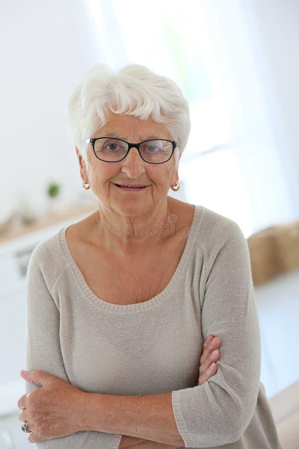 Χαμογελώντας ηλικιωμένη γυναίκα με καθιερώνοντα τη μόδα eyeglasses στοκ φωτογραφία με δικαίωμα ελεύθερης χρήσης
