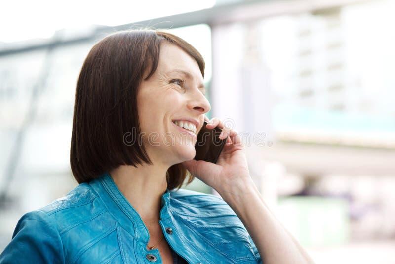 Χαμογελώντας ηλικιωμένη γυναίκα που χρησιμοποιεί το κινητό τηλέφωνο στοκ φωτογραφίες