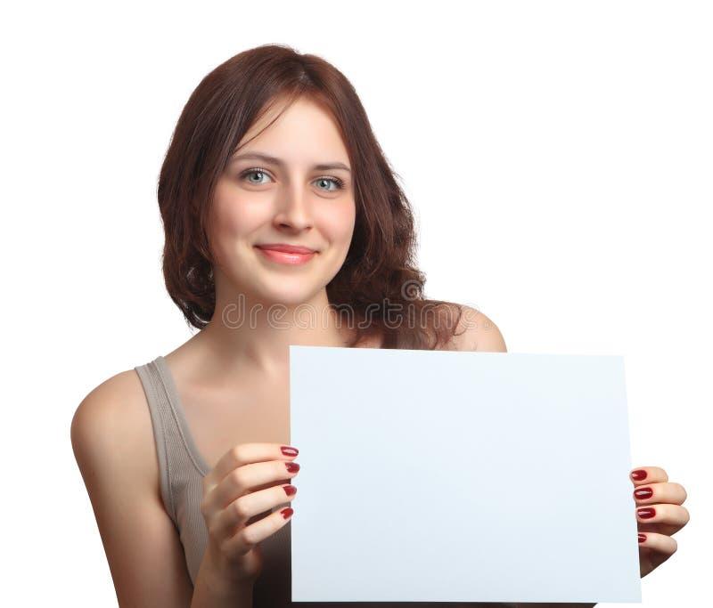 Χαμογελώντας, η καυκάσια γυναίκα 18 χρονών, παρουσιάζει κενό πίνακα σημαδιών. στοκ φωτογραφία