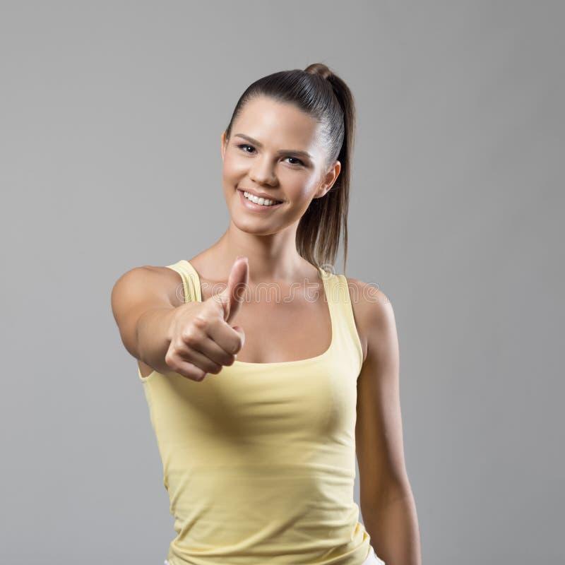 Χαμογελώντας θετική κατάλληλη γυναίκα στον κίτρινο τοπ παρουσιάζοντας αντίχειρα δεξαμενών επάνω στη χειρονομία στοκ φωτογραφίες