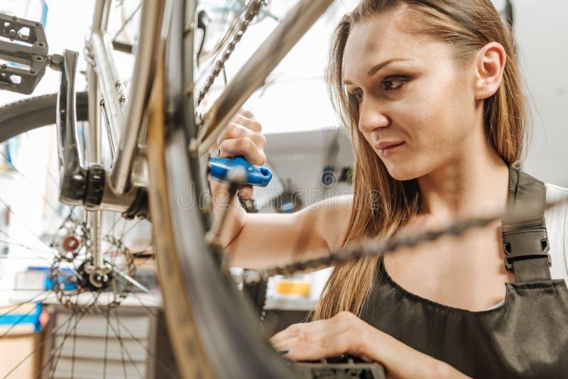 Χαμογελώντας θετικός τεχνικός που επισκευάζει το πεντάλι στο εργαστήριο στοκ φωτογραφία