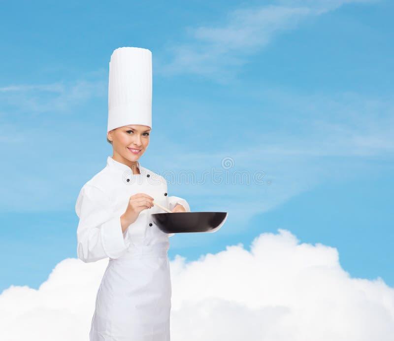Χαμογελώντας θηλυκός αρχιμάγειρας με το τηγάνι και το κουτάλι στοκ εικόνες