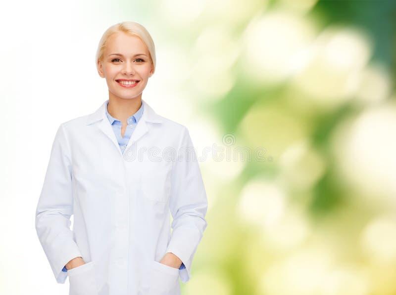 Χαμογελώντας θηλυκός γιατρός πέρα από το φυσικό υπόβαθρο στοκ φωτογραφία