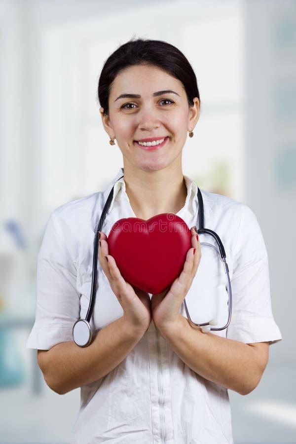 Χαμογελώντας θηλυκός γιατρός που κρατά την κόκκινη καρδιά και stethascope στοκ εικόνες με δικαίωμα ελεύθερης χρήσης