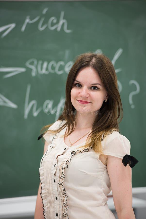 Χαμογελώντας θηλυκός φοιτητής πανεπιστημίου μπροστά από τον πίνακα στοκ εικόνες με δικαίωμα ελεύθερης χρήσης