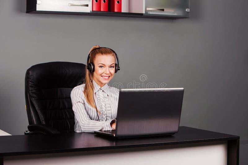 Χαμογελώντας θηλυκός χειριστής γραμμών βοήθειας με τα ακουστικά στοκ εικόνα με δικαίωμα ελεύθερης χρήσης