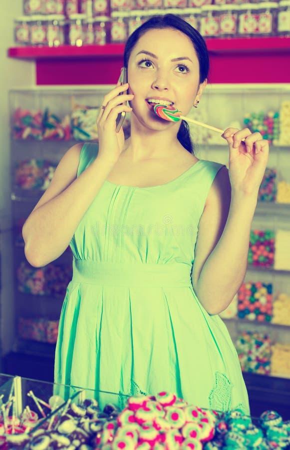 Χαμογελώντας θηλυκό που μιλά από την κινητή και καραμέλα επιλογής στοκ εικόνες