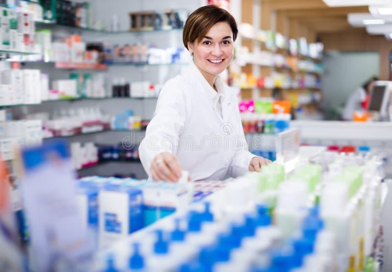 Χαμογελώντας θηλυκό που τακτοποιεί την κατάταξη των προϊόντων στοκ φωτογραφία με δικαίωμα ελεύθερης χρήσης