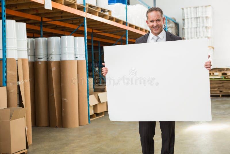 Χαμογελώντας διευθυντής αποθηκών εμπορευμάτων που κρατά τη μεγάλη άσπρη αφίσα στοκ εικόνες