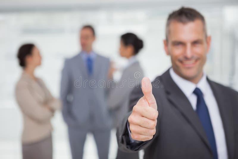 Χαμογελώντας διευθυντής που παρουσιάζει αντίχειρα με τους υπαλλήλους στο υπόβαθρο στοκ φωτογραφίες