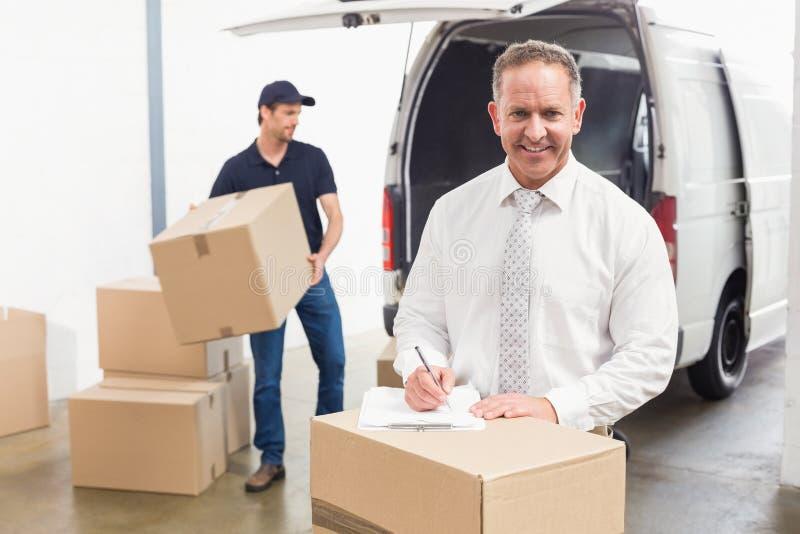 Χαμογελώντας διευθυντής που στέκεται πίσω από το σωρό των κουτιών από χαρτόνι στοκ εικόνα με δικαίωμα ελεύθερης χρήσης
