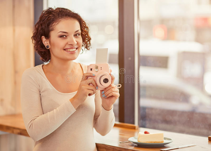 Χαμογελώντας κάμερα φωτογραφιών εκμετάλλευσης γυναικών στοκ εικόνες