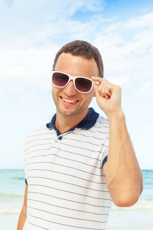 Χαμογελώντας καυκάσιο άτομο με τα γυαλιά ηλίου στην ωκεάνια ακτή στοκ φωτογραφίες