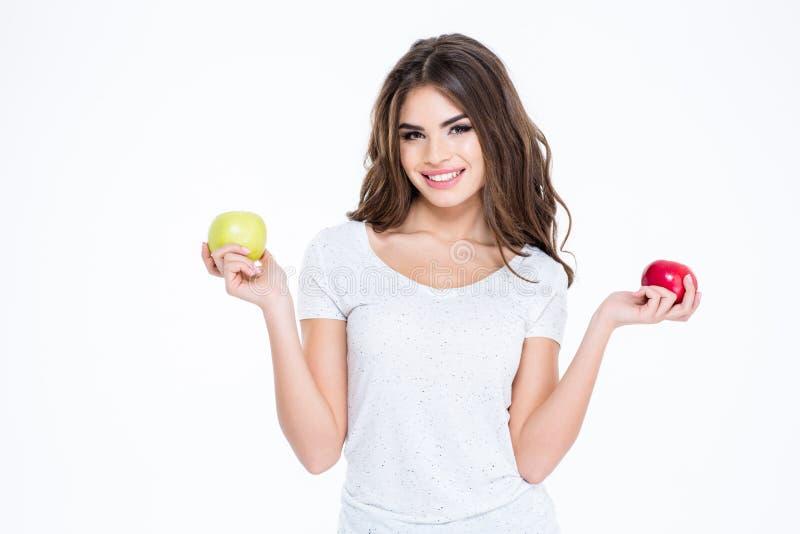 Χαμογελώντας καλή γυναίκα που κρατά δύο μήλα στοκ φωτογραφία