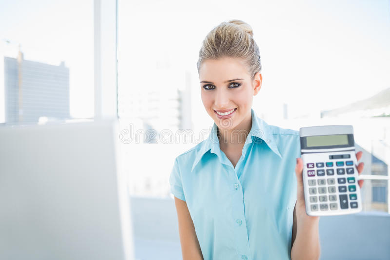 Χαμογελώντας κομψή γυναίκα που παρουσιάζει υπολογιστή στοκ εικόνες
