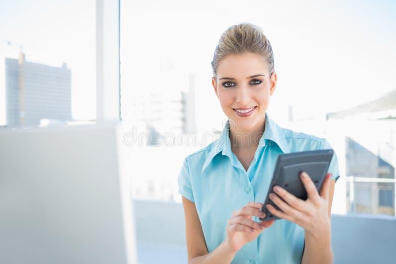 Χαμογελώντας κομψή γυναίκα που χρησιμοποιεί τον υπολογιστή στοκ εικόνα