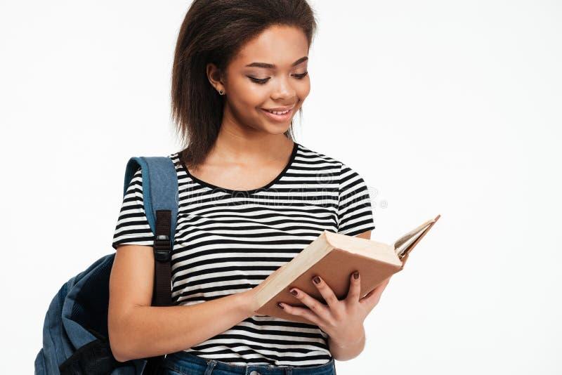 Χαμογελώντας κορίτσι εφήβων afro αμερικανικό με το βιβλίο ανάγνωσης σακιδίων πλάτης στοκ φωτογραφία