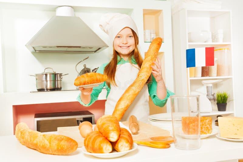 Χαμογελώντας κορίτσι με τα παραδοσιακά γαλλικά τρόφιμα αρτοποιείων στοκ εικόνα