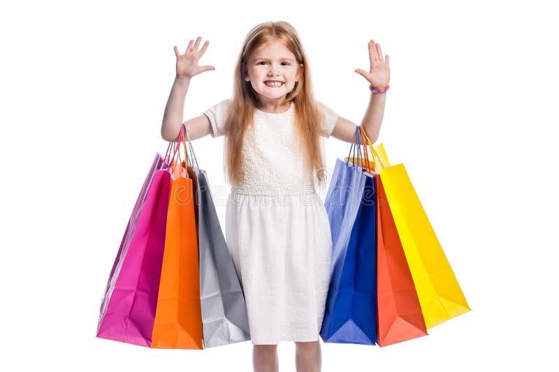 Χαμογελώντας κορίτσι με τα χέρια επάνω και τις μεγάλες ζωηρόχρωμες τσάντες αγορών στοκ εικόνες