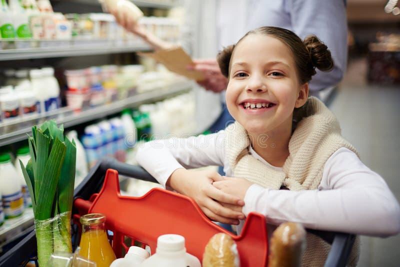 Χαμογελώντας κορίτσι με το πλήρες κάρρο αγορών στοκ φωτογραφίες