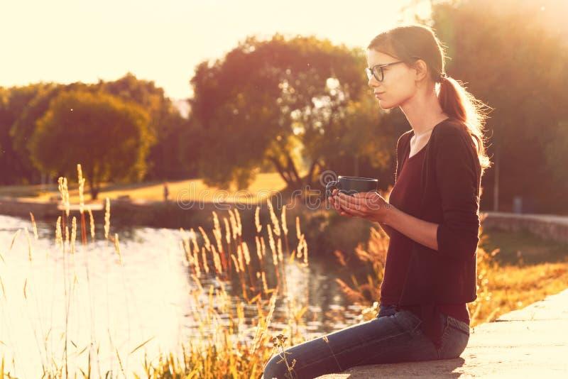 Χαμογελώντας κορίτσι με το φλυτζάνι του τσαγιού ή του καφέ που απολαμβάνει στη θερινή ακτή στοκ εικόνα