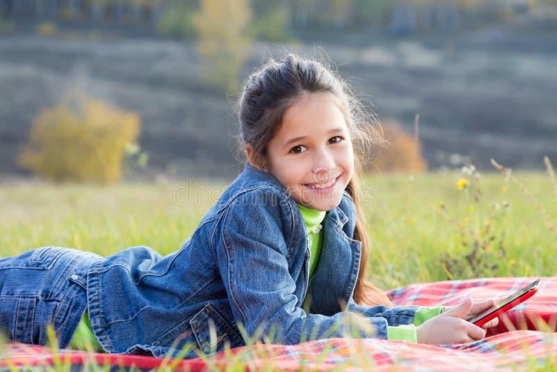 Χαμογελώντας κορίτσι με το PC ταμπλετών στοκ εικόνα