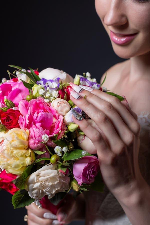 Χαμογελώντας κορίτσι νυφών χεριών όμορφο λεπτό με μια μεγάλη ανθοδέσμη του φωτεινού χρώματος στοκ εικόνες με δικαίωμα ελεύθερης χρήσης