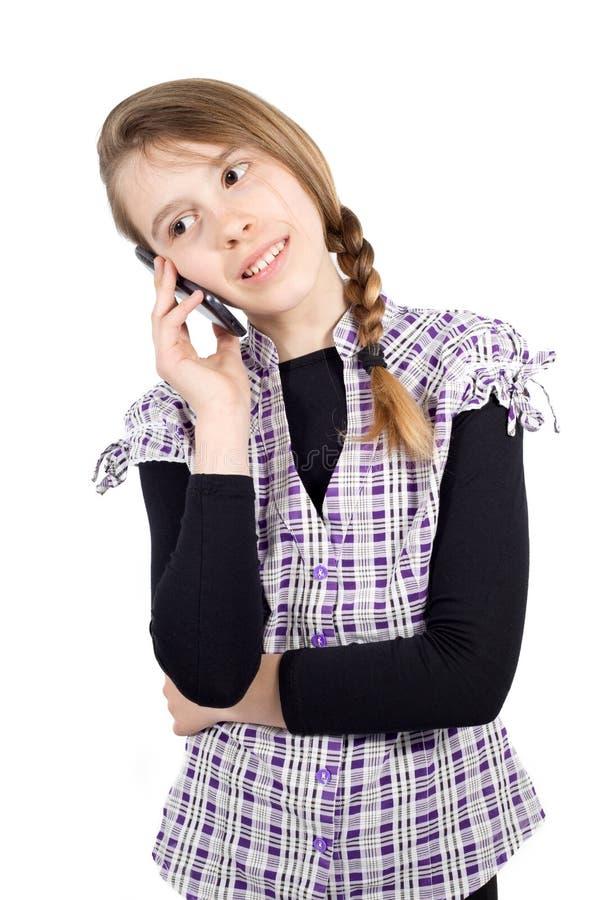 Χαμογελώντας κορίτσι που μιλά στο τηλέφωνο κυττάρων που απομονώνεται στο λευκό στοκ εικόνα
