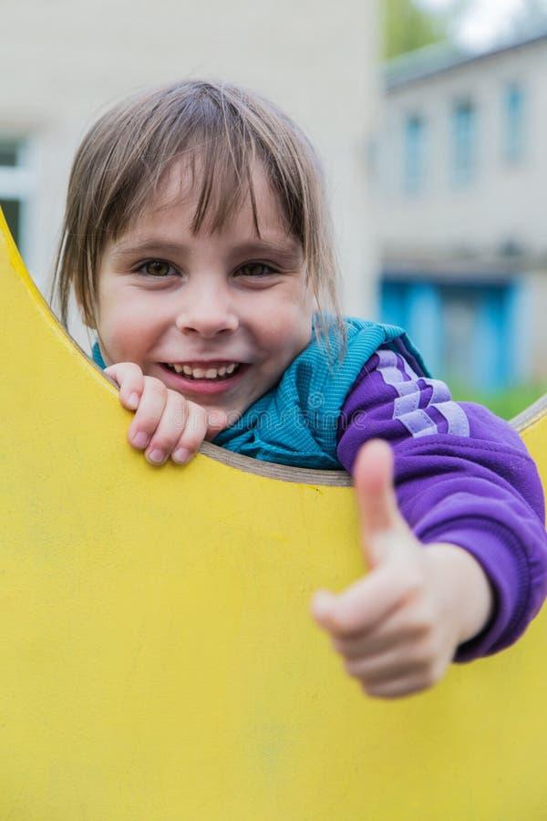 Χαμογελώντας κορίτσι που παρουσιάζει εντάξει από το παράθυρο στοκ εικόνες