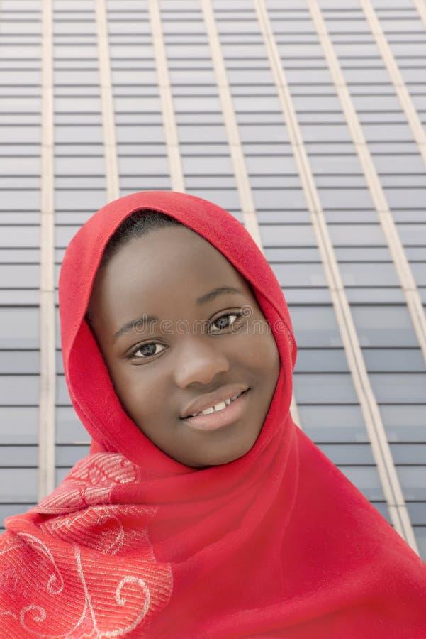 Χαμογελώντας κορίτσι που φορά ένα κόκκινο headscarf στην οδό, δέκα τρεις χρονών στοκ φωτογραφίες